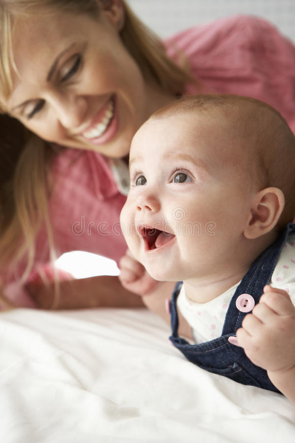 Mother With Cute Baby Girl Playing On Bed stock photo
