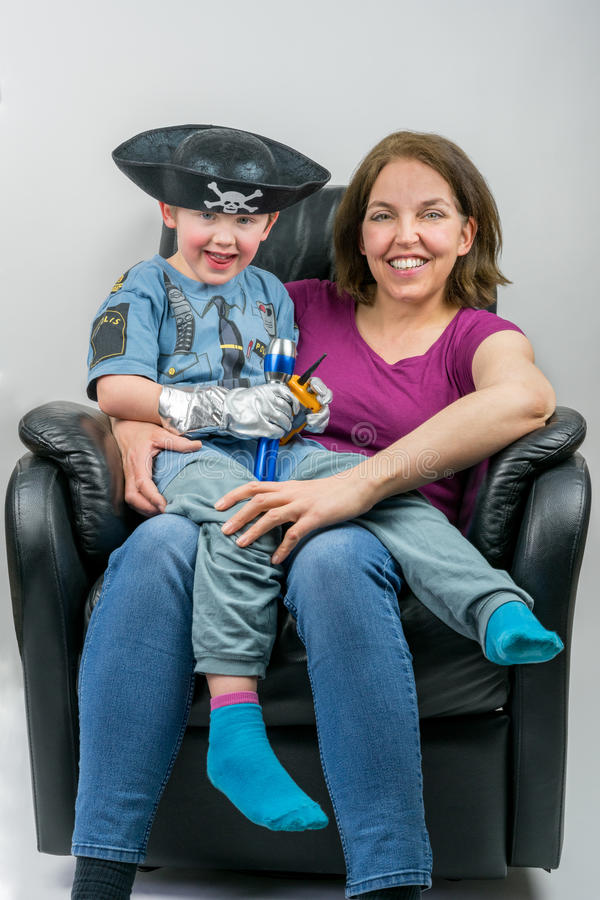 Mother and cute child dressed in pirate and police costume sitting on mother´s knee in black armchair. royalty free stock images