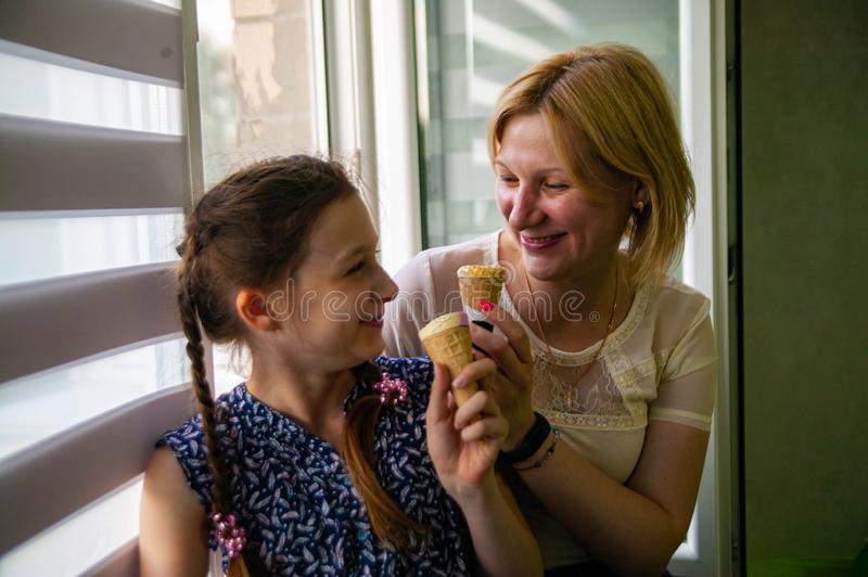 Mother and cute daughter enjoy ice cream on a hot summer day. stock image