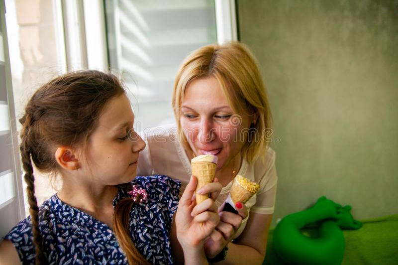 Mother and cute daughter enjoy ice cream on a hot summer day. royalty free stock photography