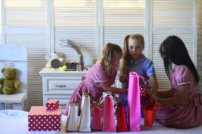Mother and cute daughters with shopping bags and packs stock photos