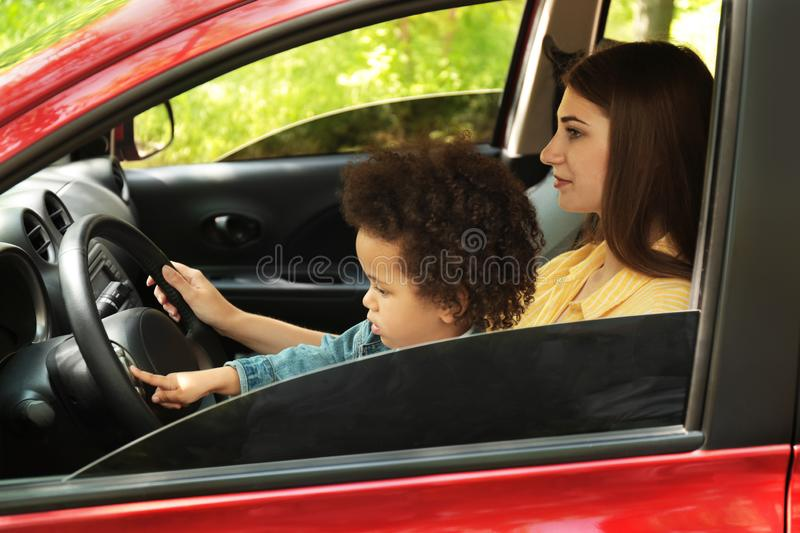 Mother with cute little daughter driving car. Child in danger stock images