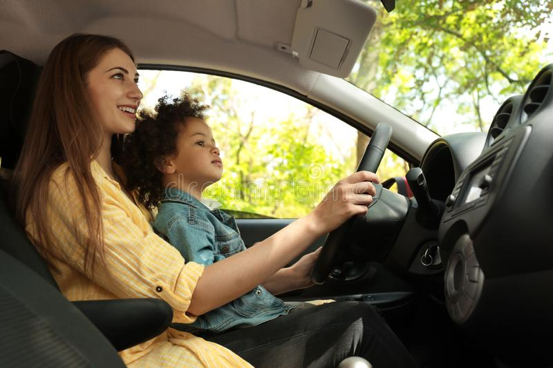 Mother with little daughter driving car together. Child in danger stock photography