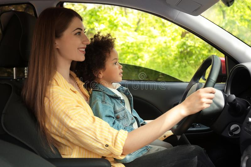 Mother with cute little daughter driving car together royalty free stock photo