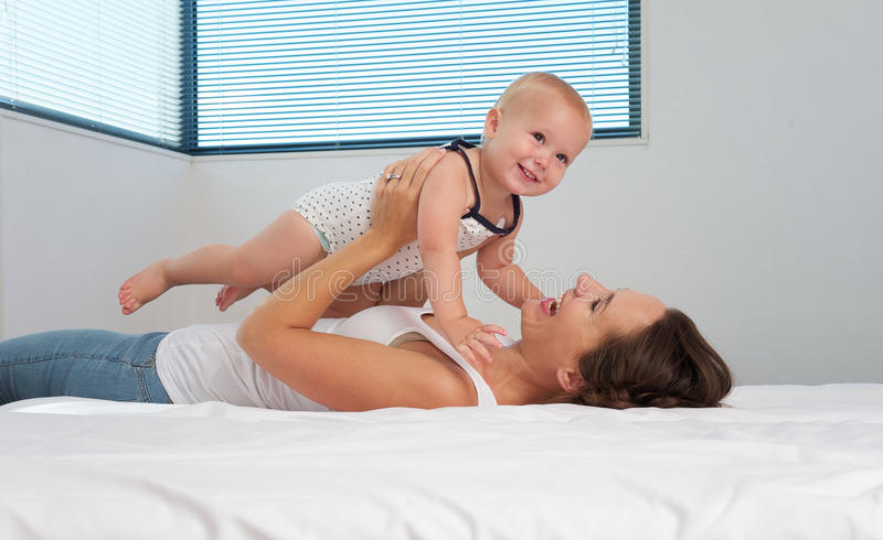 Download Mother And Cute Smiling Baby Playing In Bed Stock Photo - Image: 33847066