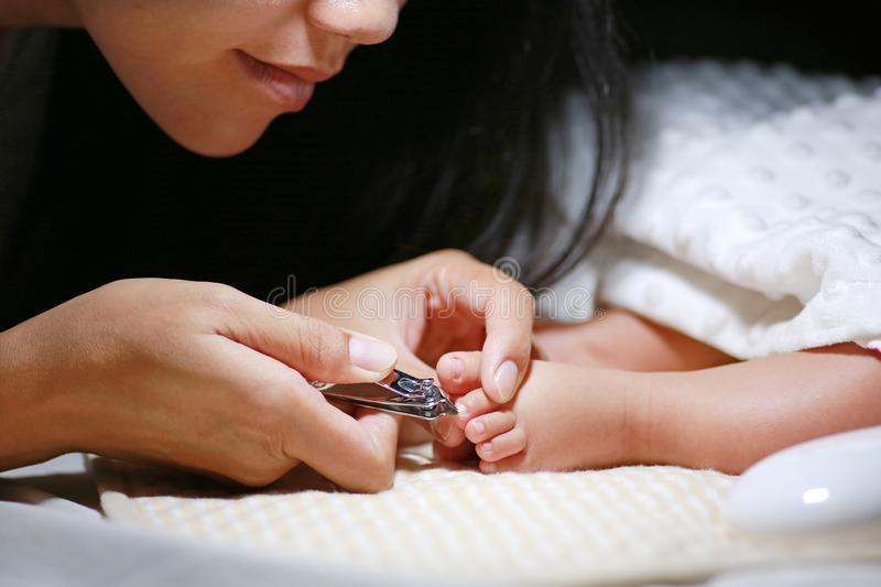 Mother cutting baby toenails. Baby care concept royalty free stock photos