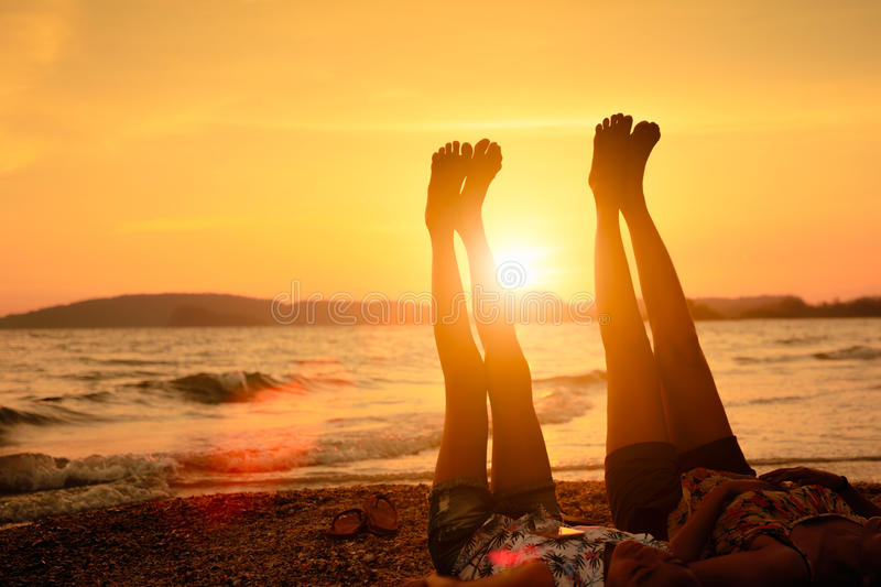 Mother and daugher on the beach. Mother and her daughter lift up they feet to sky on the beach stock photography