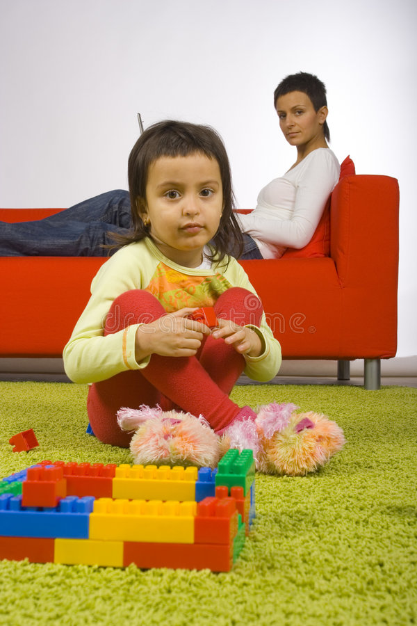 Mother and daughter. Girl sitting on the carpet and playing is watching by her busy (with laptop) mother royalty free stock images