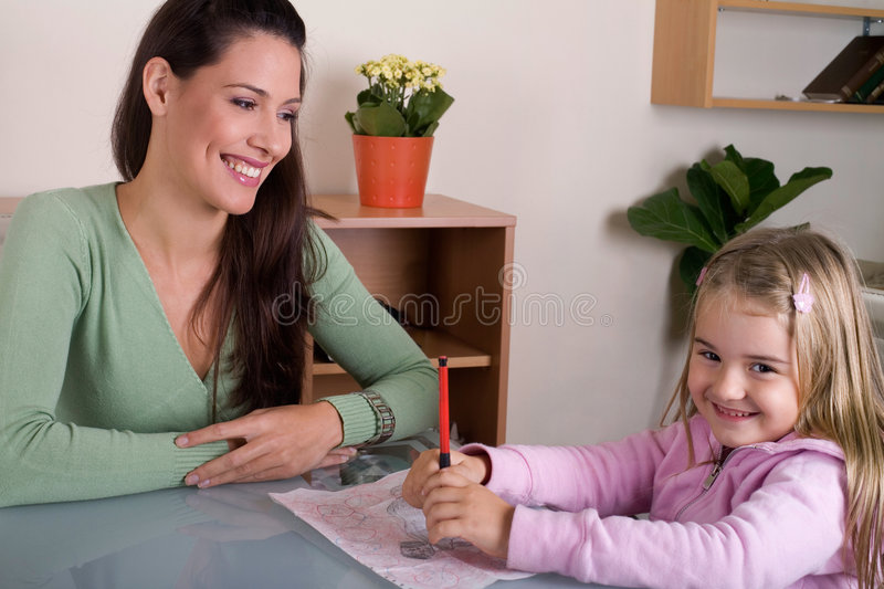 Mother an daughter. Mother is helping her daughter with homework stock images