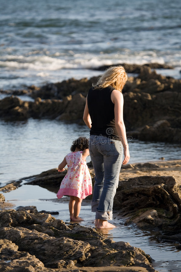 Mother and daughter. Baby daughter walking on the rocky beach with her mother