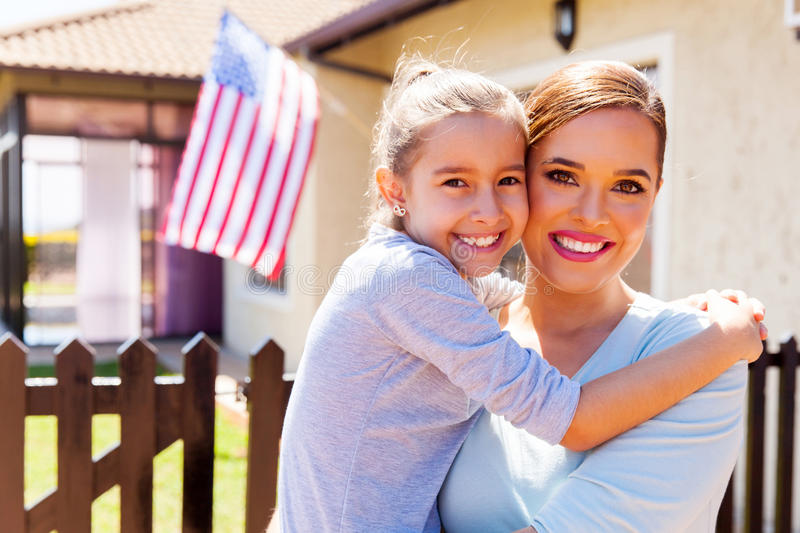 Mother daughter american flag. Happy mother and daughter with american flag outside their house royalty free stock photos