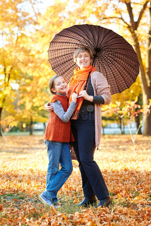 Mother and daughter are in autumn city park. Peoples are posing under umbrella. Children and parents are smiling, playing and havi royalty free stock photo