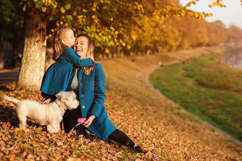 Mother and daughter on autumn walk with dog. Happy loving family having fun. Small white dog and family enjoying together outdoors royalty free stock image