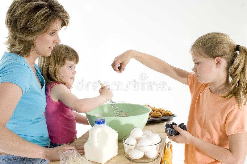 Mother Daughter Baking. Mother and two girls baking muffins. Shot in studio over white