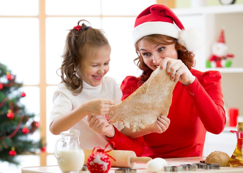 Mother and daughter baking Christmas cookies at decorated tree. Mom and child bake Xmas sweets. Family with kids. Mother and her daughter baking Christmas stock photo