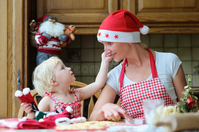 Mother and daughter baking Christmas cookies. Happy mother, young women in red apron and santa hat baking christmas cookies together with her little daughter royalty free stock image