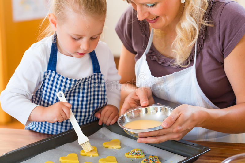 Mother and daughter baking cookies together. Baking with the family - Mother and daughter coat self made cookies with a brush royalty free stock images