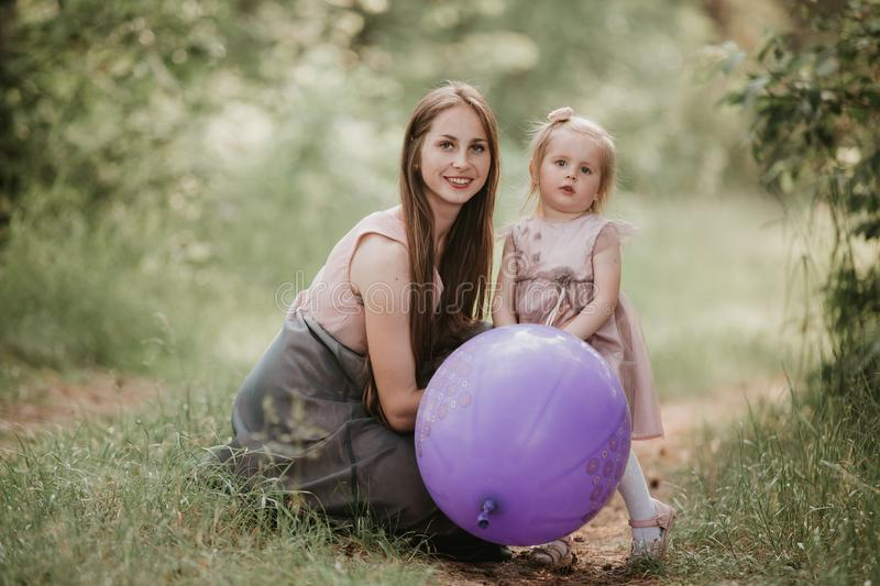 Mother and daughter with balloons. Beautiful happy mother with daughter having fun in green field holding balloons royalty free stock photography