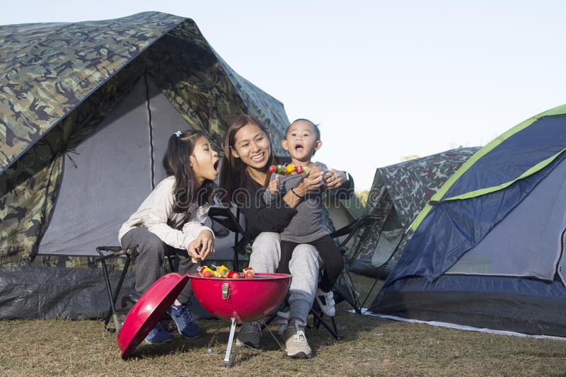 Mother and daughter barbecue on camping stock photo