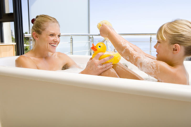 Mother and daughter (6-8) in bath outdoors, woman with rubber duck, smiling at each other. Mother and daughter (6-8) in bath outdoors, women with rubber duck stock images