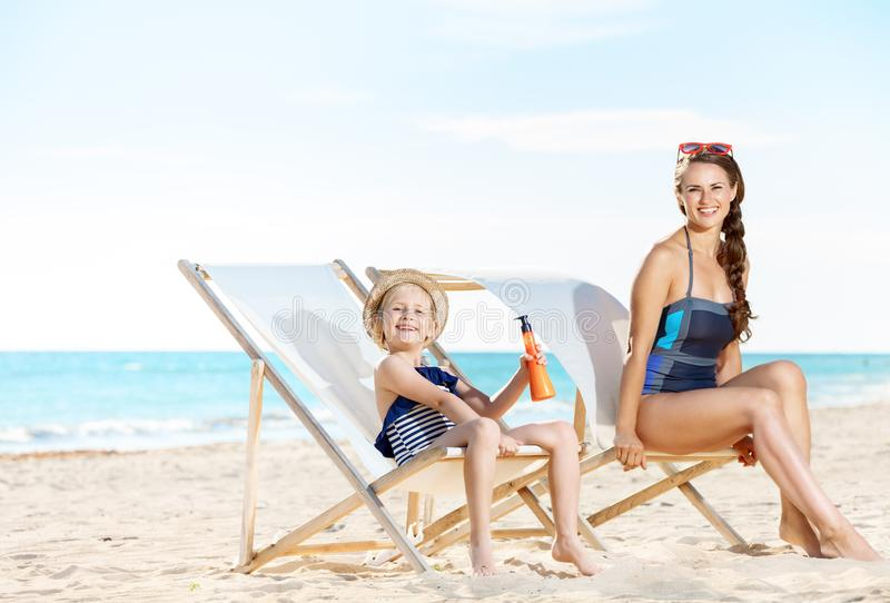 Mother and daughter on beach chairs and holding sun screen royalty free stock photos