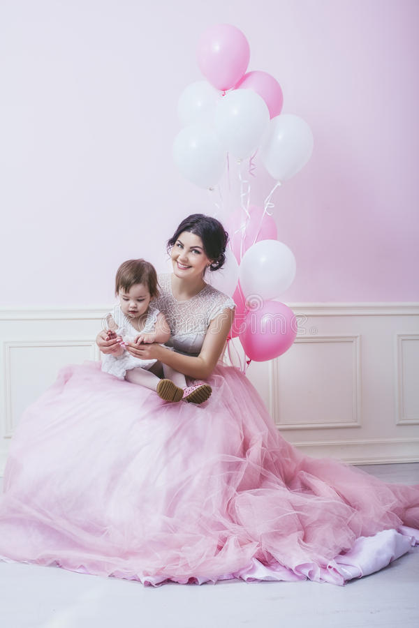Mother and daughter a beautiful and happy pink interior with vintage chair and balls in beautiful dresses. Holiday royalty free stock photos
