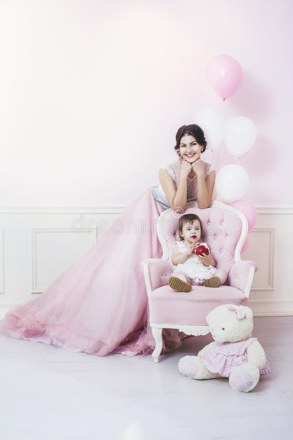Mother and daughter a beautiful and happy pink interior with vintage chair and balls in beautiful dresses royalty free stock images
