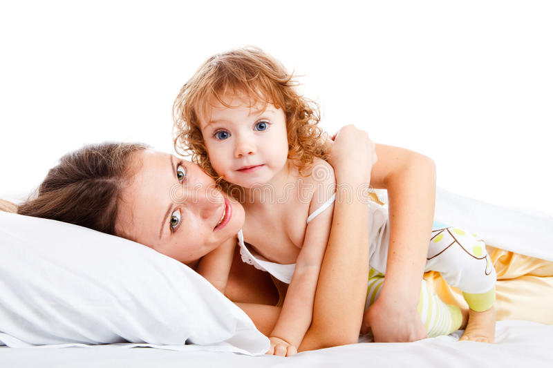 Mother and daughter in bed. Beautiful mother and daughter lying in bed royalty free stock photo