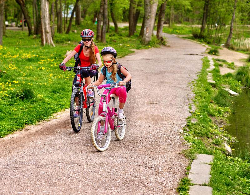 Mother and daughter on bicycle. Bikes cycling family. Happy mother teaching daughter to ride bike. Kid practice to riding lady bicycle. Friendship between stock photo
