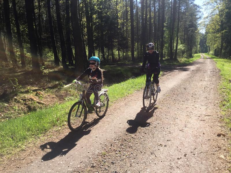 Mother and daughter on bikes in forest path stock images