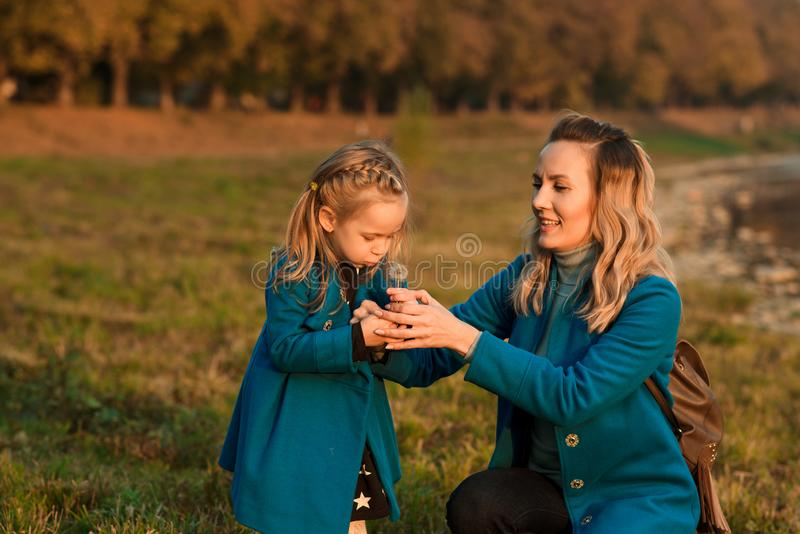 Mother and daughter blowing dandelion. Happy mother enjoying with her little daughter outdoors. Autumn fashion. Stylish mother and royalty free stock photo