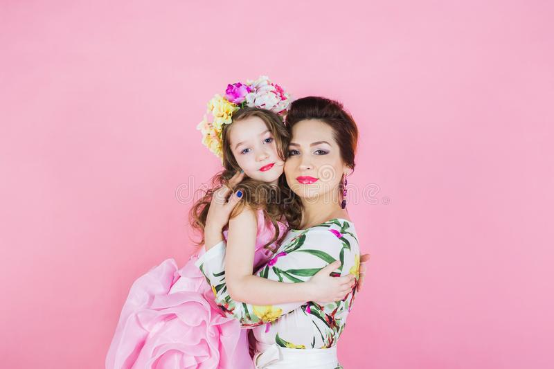 Mother and daughter in bright dresses on a pink background stock images