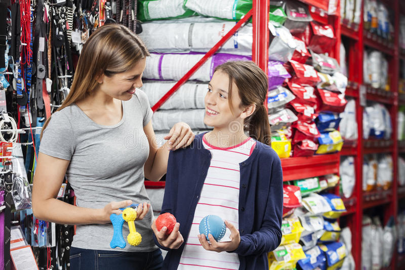 Mother And Daughter Buying Toys In Pet Store. Happy mother and daughter looking at each other while buying toys in pet store stock photos