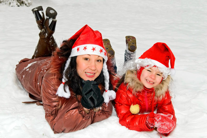 Mother and daughter in caps of Santa Claus royalty free stock photos
