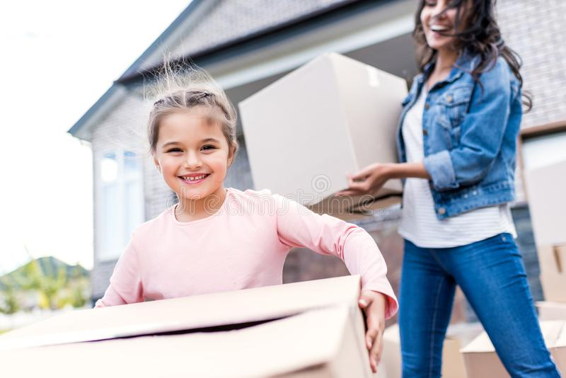 mother and daughter carrying boxes for moving into stock images