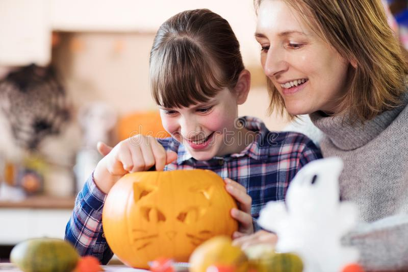 Mother And Daughter Carving Halloween Lantern From Pumpkin At Home stock photography