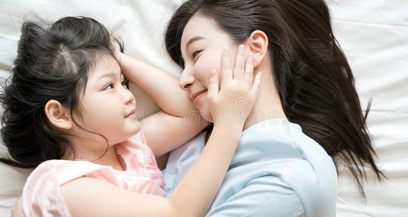 Mother and daughter child girl spending time together in the bedroom Look at each other and smiling .Happy Asian family. stock photos