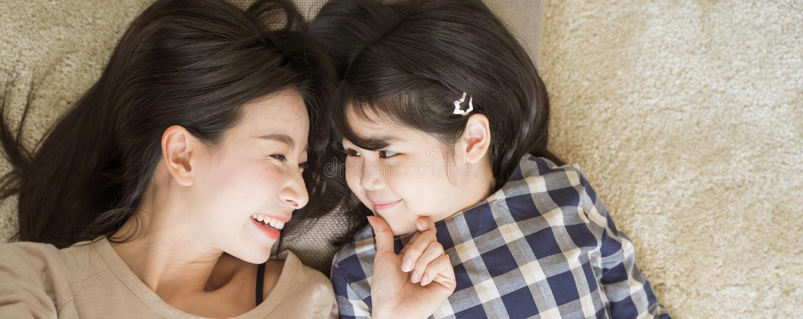 Mother and daughter child girl spending time together in the bedroom Look at each other and smiling .Happy Asian family. royalty free stock images