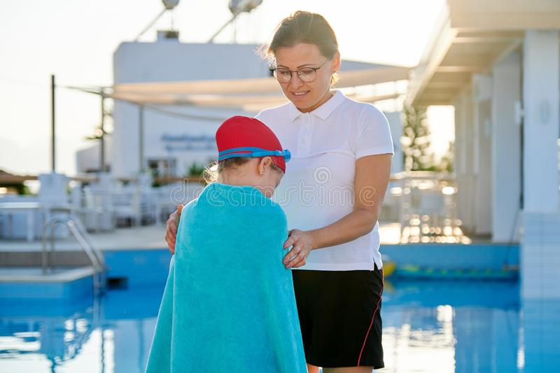 Mother and daughter child in hat goggles for swimming with towel near pool stock photos