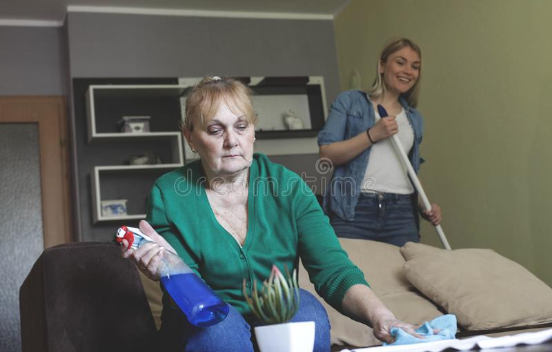 Mother and daughter cleaning together. Senior mother and young daughter cleaning house royalty free stock images