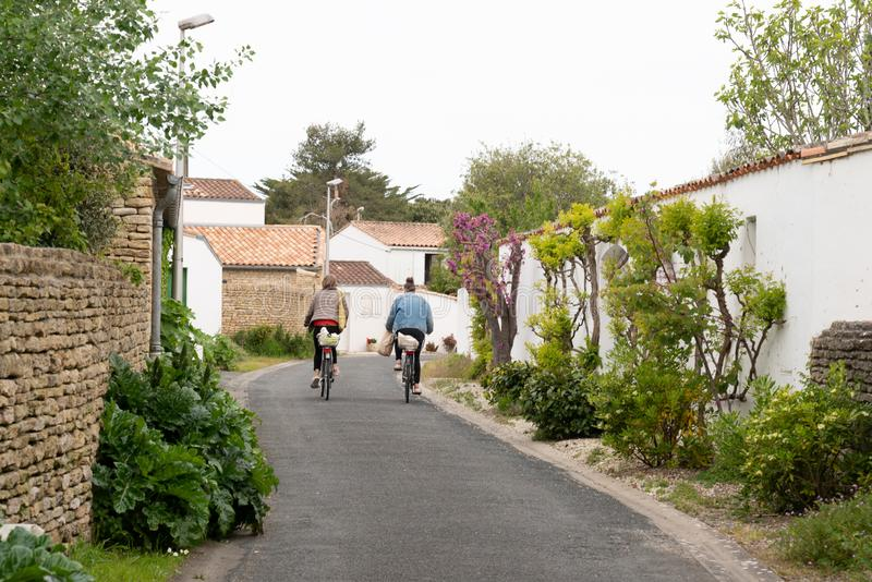 Mother and daughter come back from the market of the Ile de Ré by bike in the alley in France stock images