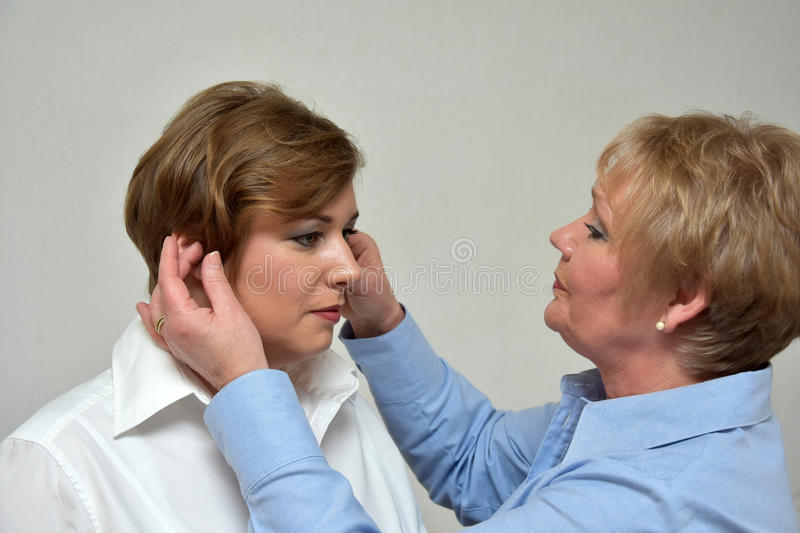 Mother and daughter. Mother controls outfit and makeup of her daughter stock photos