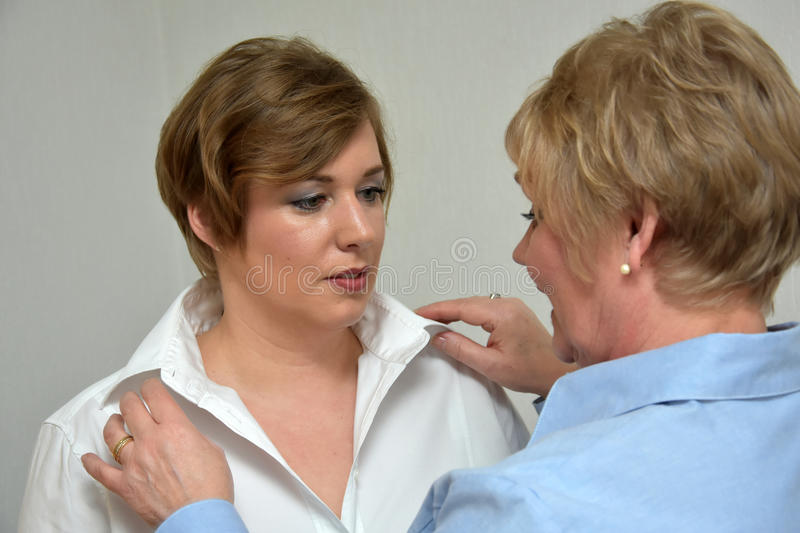 Mother and daughter. Mother controls outfit and makeup of her daughter royalty free stock photos