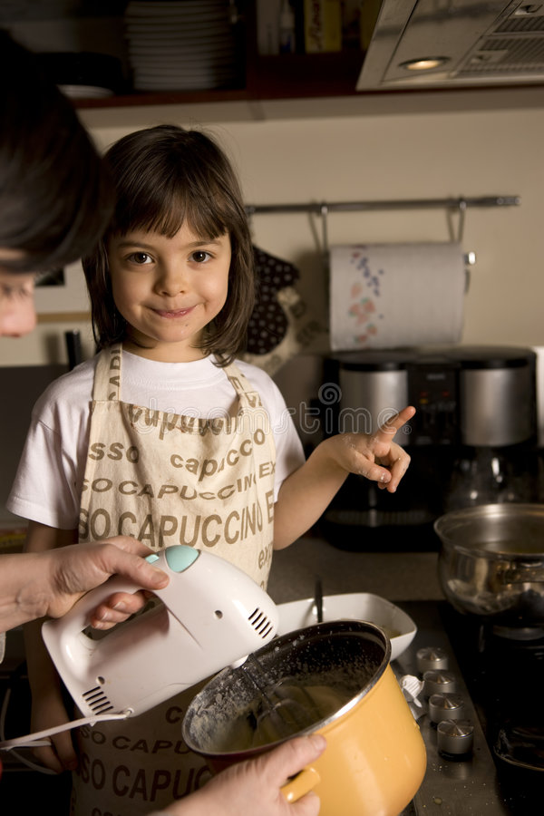 Mother and daughter cooking. Young girl having fun in the kitchen making cookies royalty free stock photography