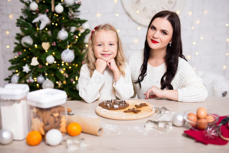 Mother and daughter cooking Christmas cookies in kitchen royalty free stock images