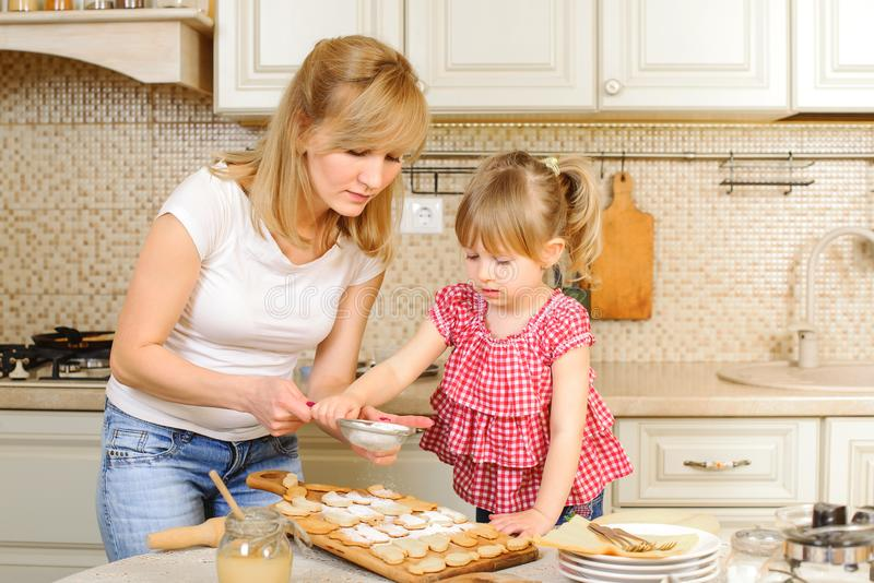 Mother and daughter are cooking cookies. Mom and child having fun in the kitchen. Homemade food and little helper. Holidays royalty free stock photos