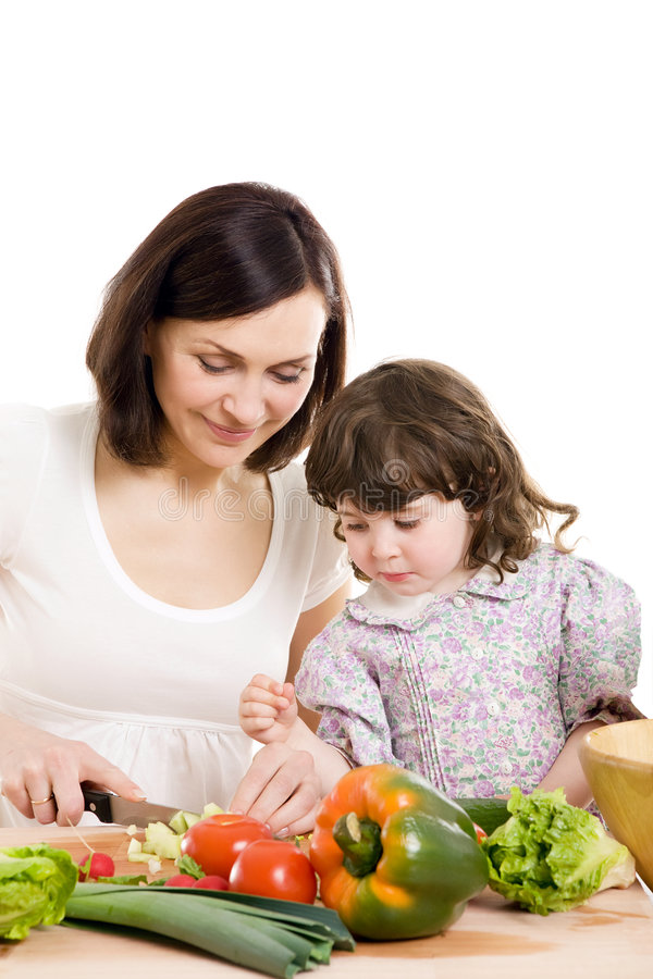 Mother and daughter cooking at the kitchen stock photo