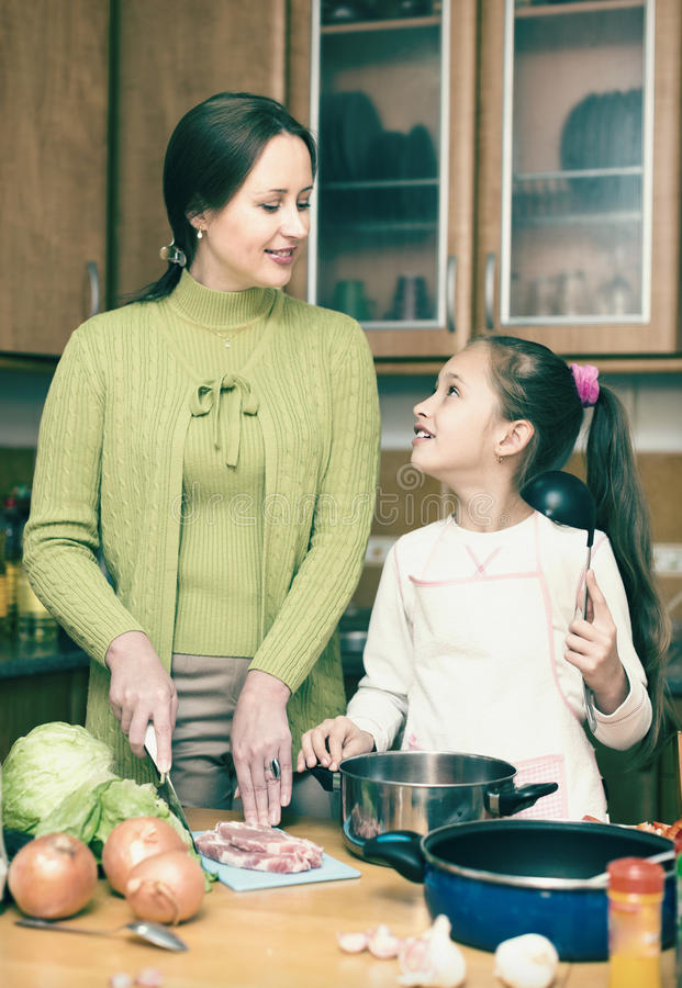 Mother with daughter cooking at kitchen royalty free stock photos