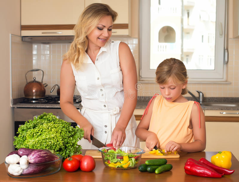 Mother and daughter cooking together, help children to parents. Healthy domestic food concept. royalty free stock photography