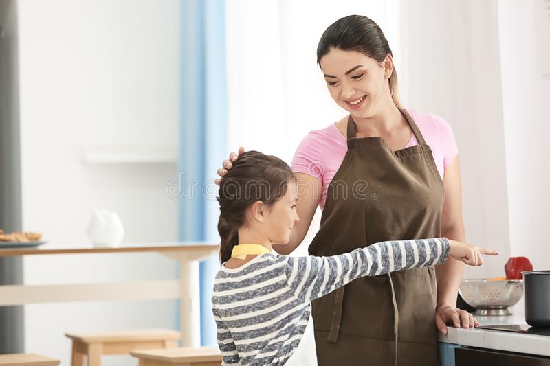 Mother and daughter cooking together in kitchen royalty free stock photography
